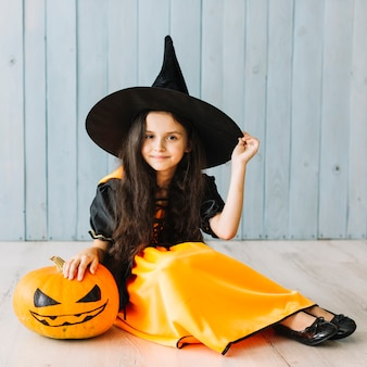 Smiling little witch sitting with pumpkin on floor