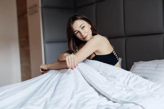 Улыбающаяся длинноволосая брюнетка на белой кровати в мягком утреннем свете под одеялом