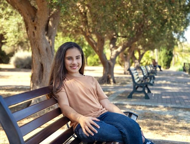 Улыбающаяся латиноамериканская девушка с длинными волосами в бежевой футболке и джинсах сидит на скамейке на открытом воздухе