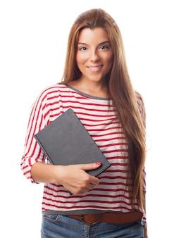 Smiling long haired brunette holding black notebook