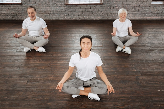 Smiling long-haired trainer wearing white t-shirt and grey trousers crossing his legs while sitting in yoga position