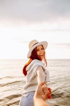 Smiling long haired woman in a hat holding boyfriends hand along empty ocean beach sand at sunset