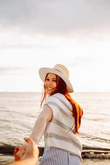Smiling long haired woman in a hat runs holding boyfriend hand along empty ocean beach sand at sunset