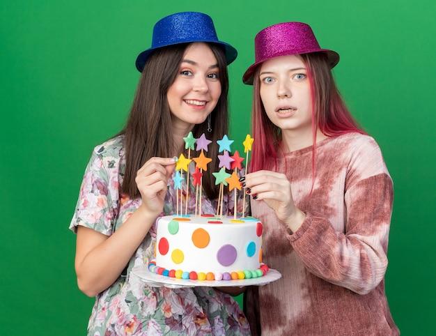 ケーキを保持しているパーティーハットを身に着けているカメラの女の子を見て笑顔