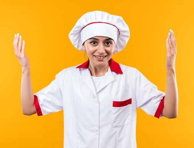 카메라를 보고 웃고 있는 요리사 제복을 입은 아름다운 소녀가 손을 들고 있습니다.