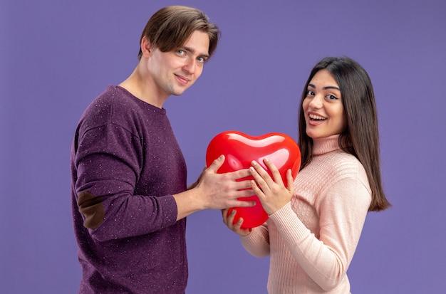 青い背景で隔離のハートの風船を保持してバレンタインデーにカメラの若いカップルを見て笑顔