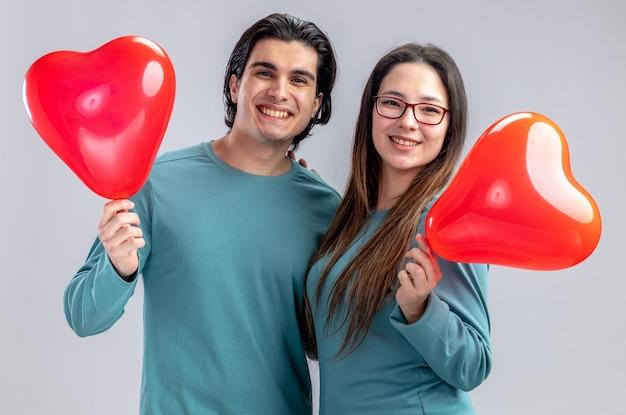白い背景で隔離のハートの風船を保持してバレンタインデーにカメラの若いカップルを見て笑顔