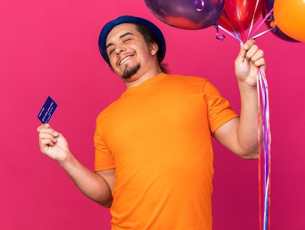 クレジットカードで風船を保持しているパーティーハットを身に着けているカメラの若い男を見て笑顔