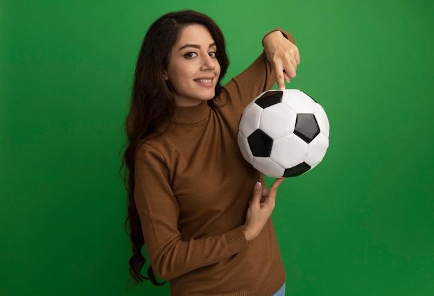 녹색 벽에 고립 된 손가락에 공을 들고 앞 젊은 아름 다운 소녀를보고 웃 고
