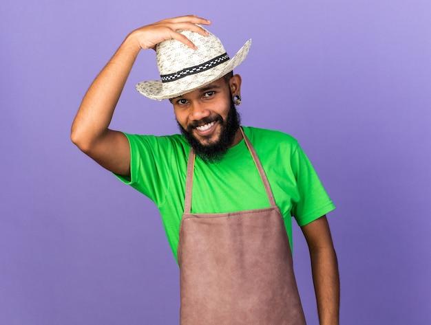파란 벽에 격리된 원예 모자를 쓴 앞의 젊은 정원사 아프리카계 미국인 남자를 바라보며 웃고 있습니다.