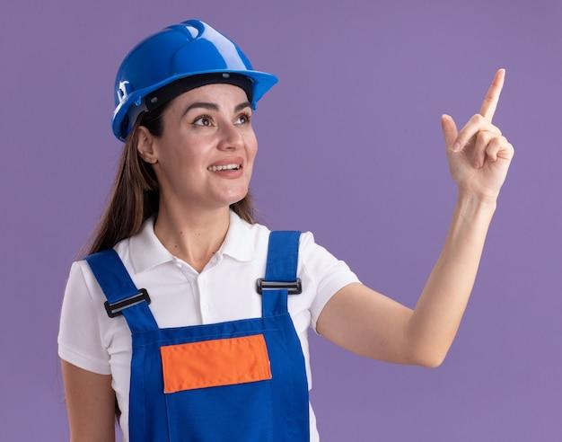 Улыбаясь, глядя на сторону, молодая женщина-строитель в униформе указывает сбоку, изолированную на фиолетовой стене