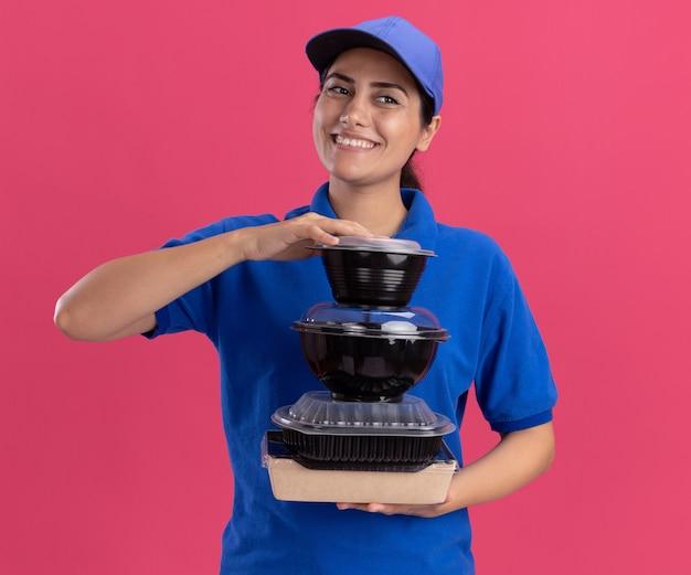 Улыбаясь, глядя в сторону, молодая доставщица в униформе с кепкой держит контейнеры для еды на розовой стене
