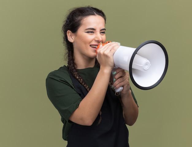 제복을 입은 측면 젊은 여성 이발사를보고 웃 고 올리브 녹색 벽에 고립 된 스피커에 말한다
