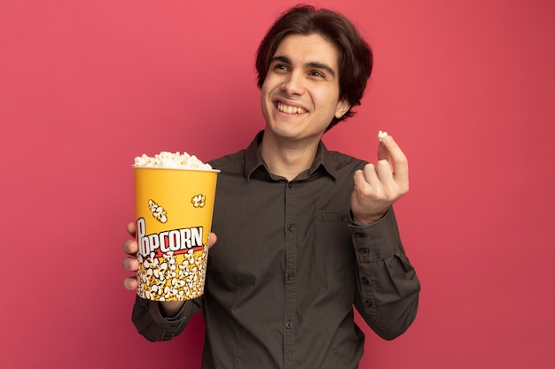 핑크 벽에 고립 된 팝콘 평화와 팝콘의 양동이를 들고 검은 티셔츠를 입고 측면 젊은 잘 생긴 남자를보고 웃고