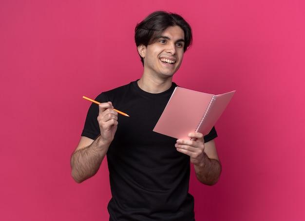 분홍색 벽에 고립 된 연필로 노트북을 들고 검은 티셔츠를 입고 측면 젊은 잘 생긴 남자를보고 웃 고