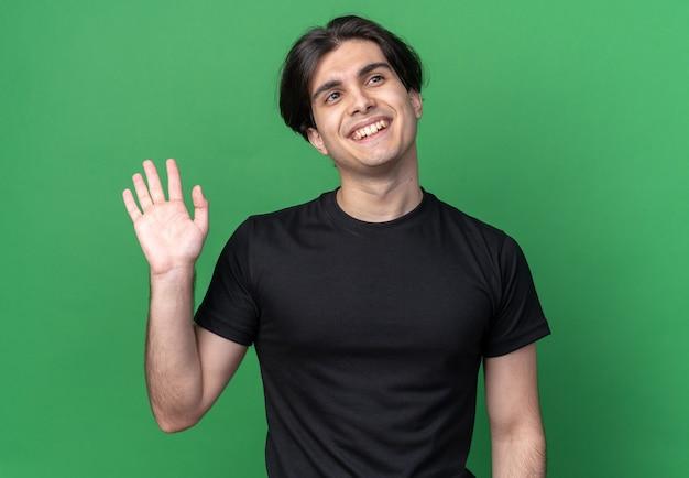 緑の壁に分離されたこんにちはジェスチャーを示す黒い t シャツを着た若いハンサムな男の側を見て笑顔