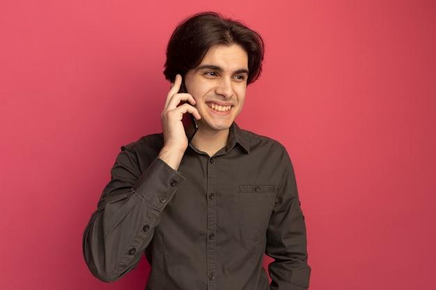 검은 티셔츠를 입고 측면 젊은 잘 생긴 남자를보고 웃고 분홍색 벽에 고립 된 전화에 말한다