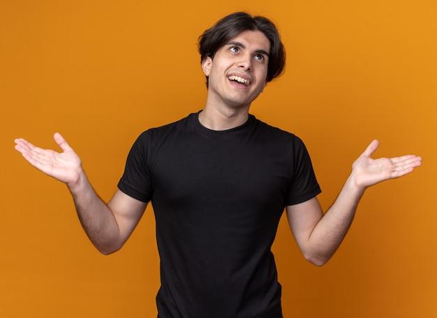 오렌지 벽에 고립 된 손을 확산 검은 티셔츠를 입고 측면 젊은 잘 생긴 남자를보고 웃고
