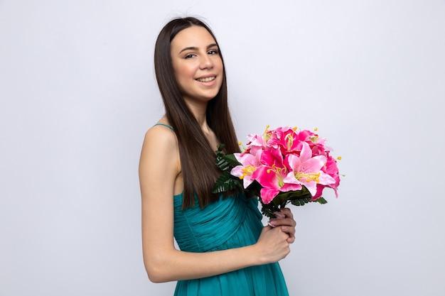 Sorridente cerca macchina fotografica bella ragazza sulla festa della donna felice che tiene il mazzo isolato sul muro bianco