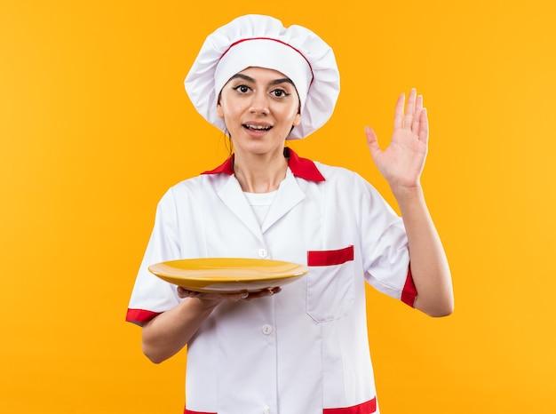 Sorridente guardando la telecamera giovane bella ragazza in uniforme da chef che tiene la piastra alzando la mano