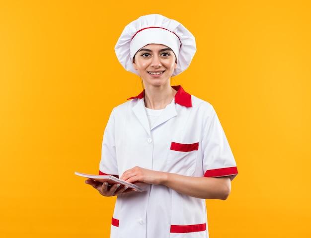 Sorridente guardando la telecamera giovane bella ragazza in uniforme da chef notebook