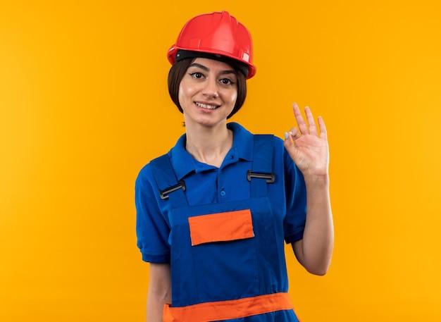 Sorridente guardando la telecamera giovane donna costruttore in uniforme che mostra gesto ok