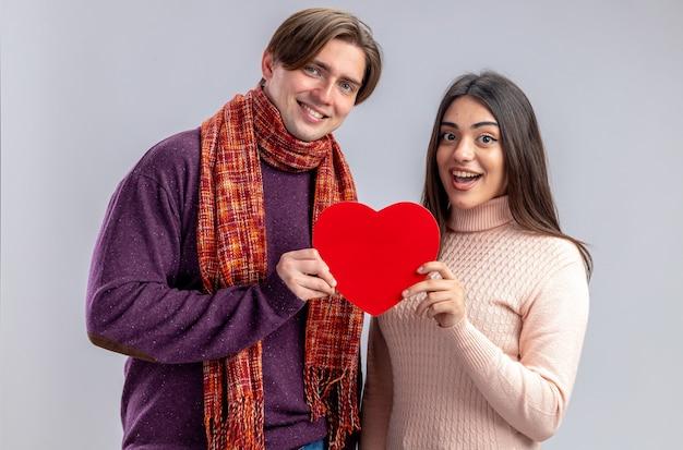 Sorridente guardando fotocamera giovane coppia il giorno di san valentino che tiene scatola a forma di cuore isolata su sfondo bianco