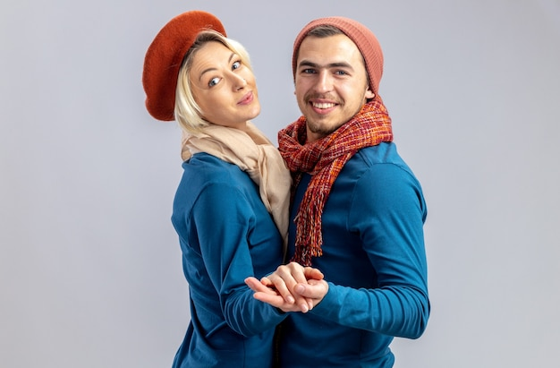 Sorridente guardando fotocamera giovane coppia il giorno di san valentino indossando cappello con sciarpa danza isolato su sfondo bianco