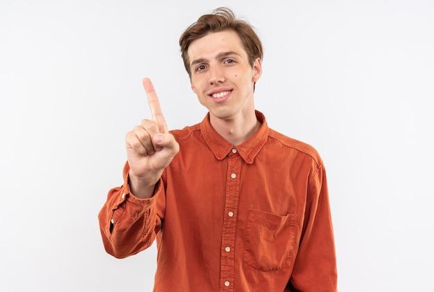 Sorridente guardando fotocamera giovane bel ragazzo che indossa una camicia rossa che mostra uno isolato sul muro bianco