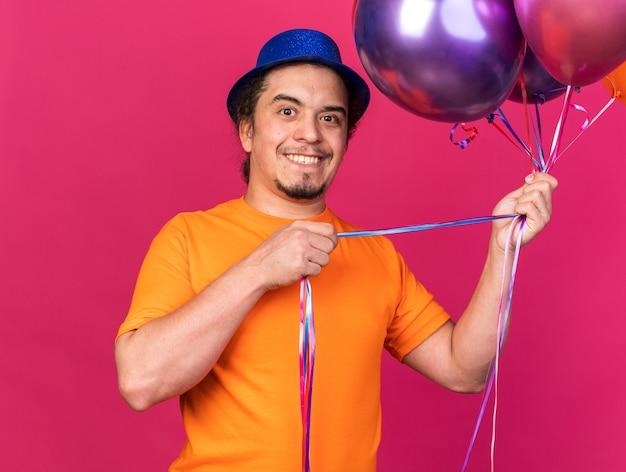 Sorridente cercando fotocamera giovane uomo che indossa cappello da festa tenendo palloncini isolati su parete rosa