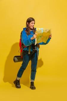 笑顔で道を探しています。黄色のスタジオの背景に分離されたバッグと双眼鏡で陽気な若い白人観光客の女の子の肖像画。旅行の準備。リゾート、人間の感情、休暇。