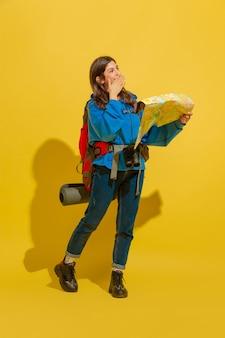 Улыбается, ищет путь. портрет веселой молодой кавказской туристической девушки с сумкой и биноклем, изолированными на желтом фоне студии.