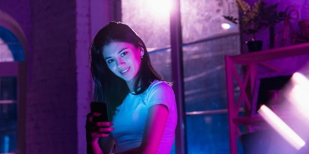 미소, 기대합니다. 네온 조명 인테리어의 세련된 여성의 영화적 초상화. 보라색 - 파란색의 영화 효과처럼 톤. 실내에서 화려한 조명으로 스마트폰을 사용하는 백인 여성 모델.