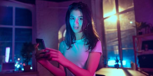 미소, 기대합니다. 네온 조명 인테리어에 세련된 여성의 영화적 초상화. 보라색 - 파란색의 영화 효과처럼 톤. 실내에서 화려한 조명으로 스마트폰을 사용하는 백인 모델입니다. 전단.