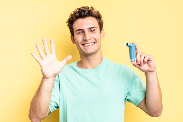 Smiling and looking friendly, showing number five or fifth with hand forward, counting down. asthma concept