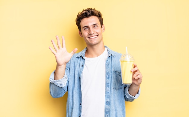 Smiling and looking friendly, showing number five or fifth with hand forward, counting down. milkshake concept