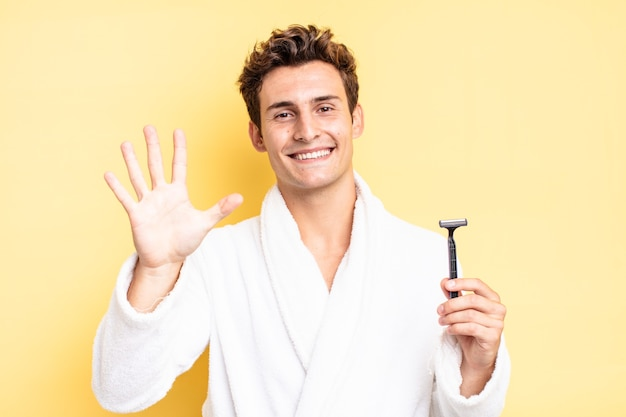Smiling and looking friendly, showing number five or fifth with hand forward, counting down. shave concept