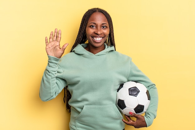 Smiling and looking friendly, showing number five or fifth with hand forward, counting down. soccer concept