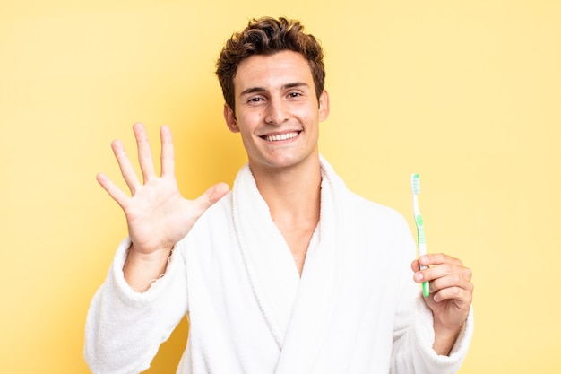 Smiling and looking friendly, showing number five or fifth with hand forward, counting down. tooth brush concept