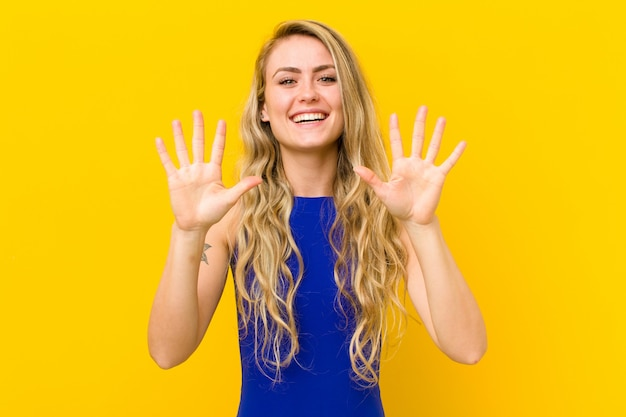 Smiling and looking friendly, showing number ten or tenth with hand forward, counting down