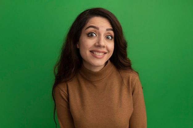 Sorridente guardando davanti giovane bella ragazza isolata sulla parete verde