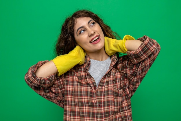 笑顔の側をつかんだ首の若い掃除をしている女性が手袋をはめている
