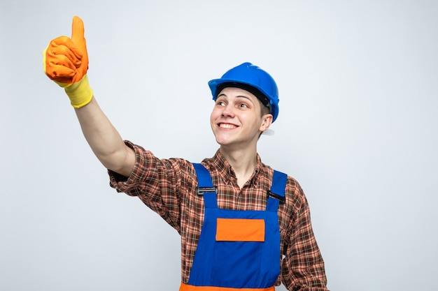 Smiling looking side showing thumb up young male builder wearing uniform with gloves