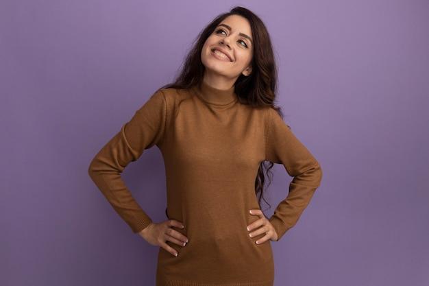 Sorridente guardando lato giovane bella ragazza che indossa un maglione dolcevita marrone che mette le mani sull'anca isolato sulla parete viola