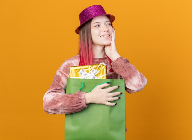 Smiling looking side young beautiful girl wearing party hat holding gift bag putting hand on cheek isolated on orange wall
