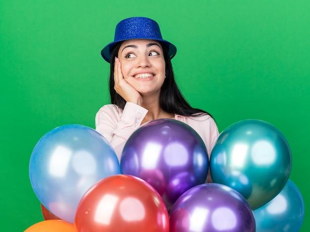 Sorridente guardando lato giovane bella ragazza che indossa un cappello da festa in piedi dietro i palloncini mettendo la mano sulla guancia isolata sul muro verde