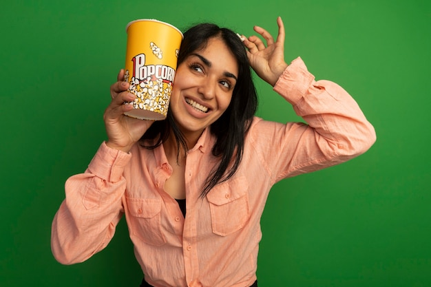 Sorridente guardando al lato giovane bella ragazza che indossa la maglietta rosa che tiene il secchio di popcorn con la pace del popcorn intorno alla testa isolata sulla parete verde