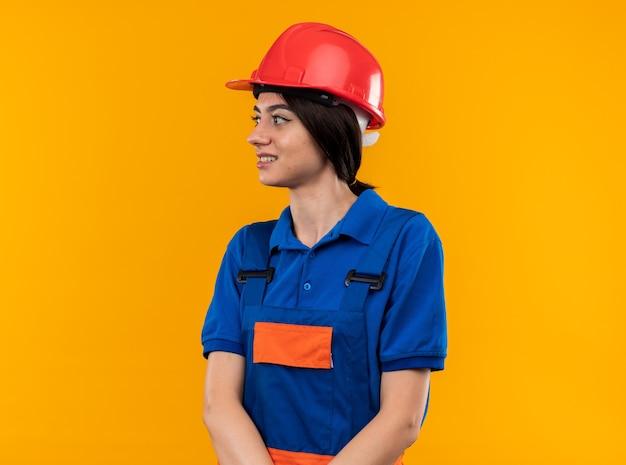 Sorridente guardando lato giovane donna costruttore in uniforme isolata sulla parete gialla con copia spazio