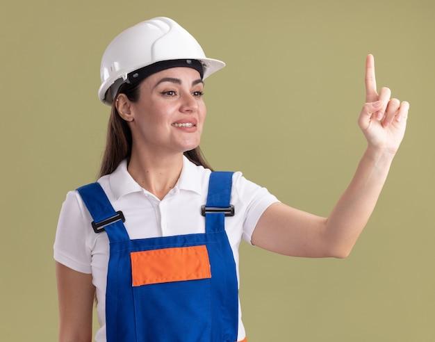 Sorridente guardando lato giovane donna costruttore in uniforme che mostra uno isolato sulla parete verde oliva
