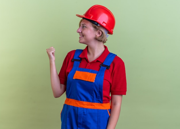 Sorridente guardando lato giovane donna costruttore in uniforme che mostra sì gesto isolato su verde oliva wall